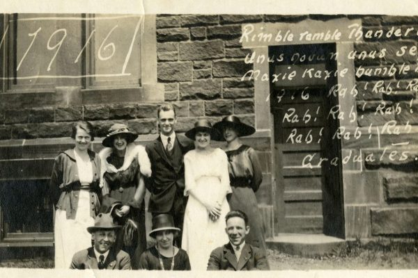Mount Allison University class of 1916 out front of the Owens with their class cheer written on the photo