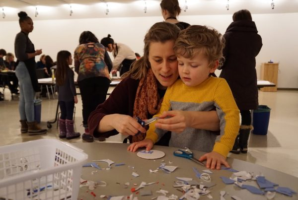 In a gallery an adult and child sit together at a table cluttered with small scraps of cut paper. The adult uses a pair of scissors to cut small pieces of paper while the child watches. Behind them adults and children work at other tables.