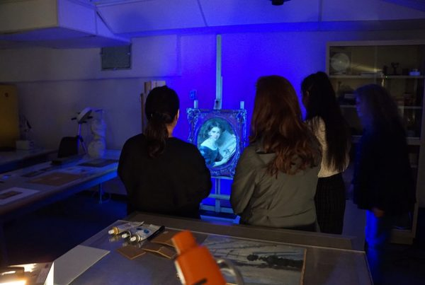 A group of adults stand in an art conservation lab examining a framed portrait painting under ultra violet light. The whole scene is cast in a blue glow.