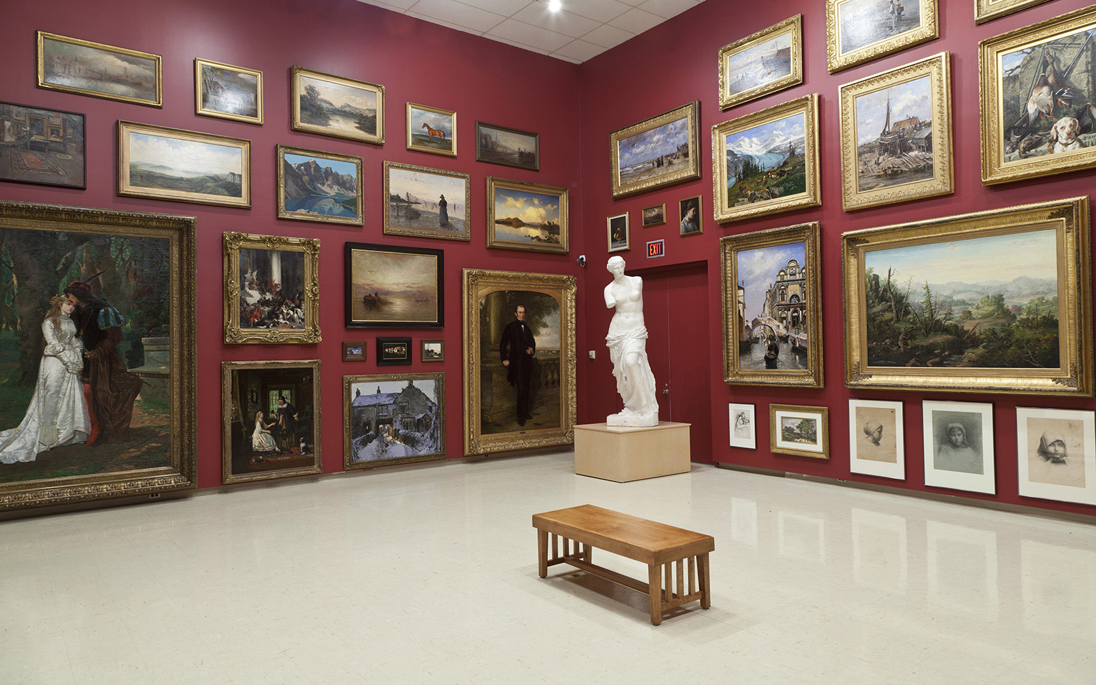 In a gallery with high ceilings, framed paintings and works on paper are hung salon style against deep red walls. A plaster cast of the Venus de Milo is displayed on a wooden plinth in the corner of the room. In the center of the room there is a wooden bench.