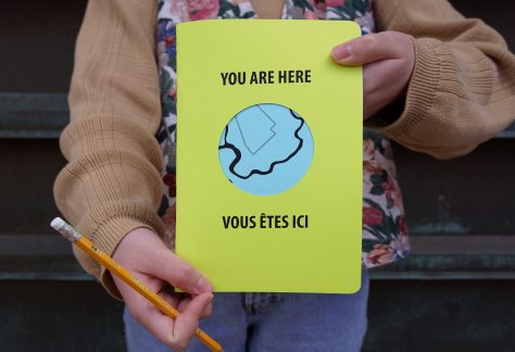"""An adult holds a pencil and bright green sketchbook. The cover reads """"You Are Here"""" and """"Vous Etes Ici"""", and a circle cut into the cover reveals a blue river on the page beneath."""