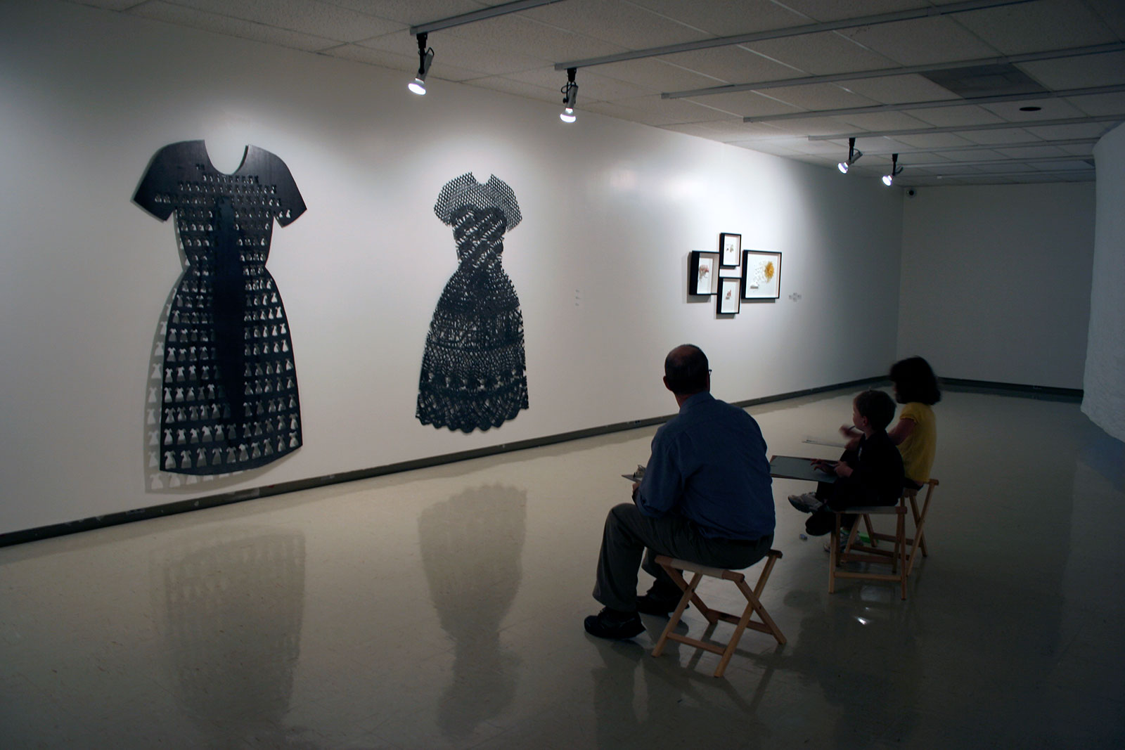 An adult and two children sit on folding stools in a darkened gallery. They hold clipboards and pencils and look towards two large, flat dress-shaped sculptures that hang on the wall.