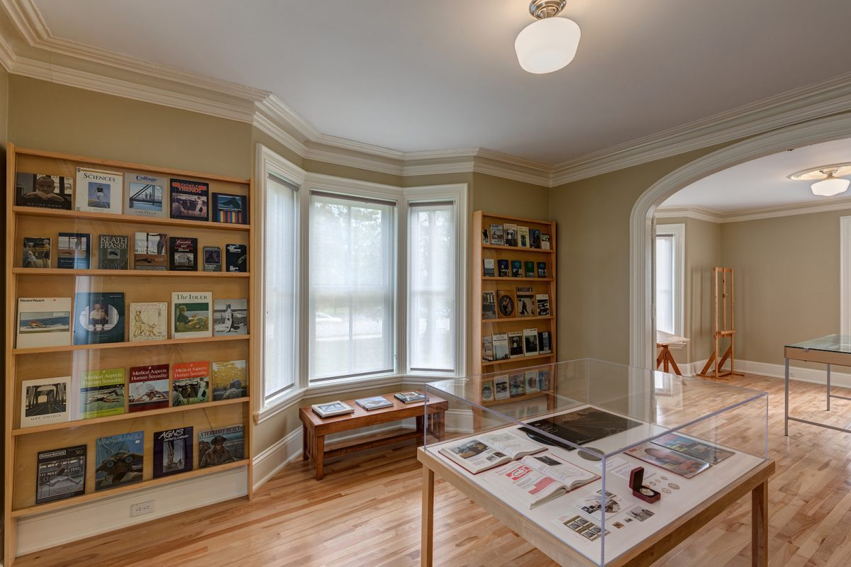 In the centre of a room, a display case holds coins, a record and books. On the walls, two shelves display several books with artworks on their covers.