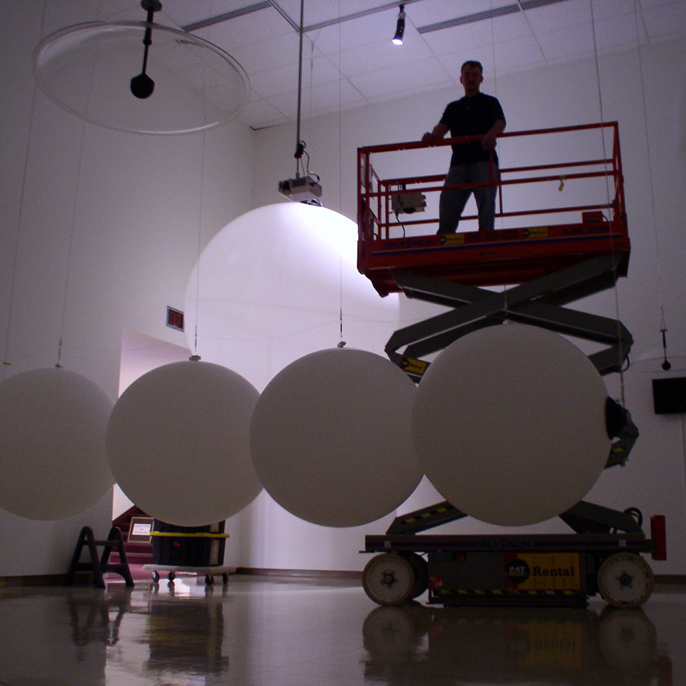 Roxie Ibbitson, Owens Art Gallery Registrar/Preparator stands silhouetted atop a scissor lift, high above a large installation of weather balloons.