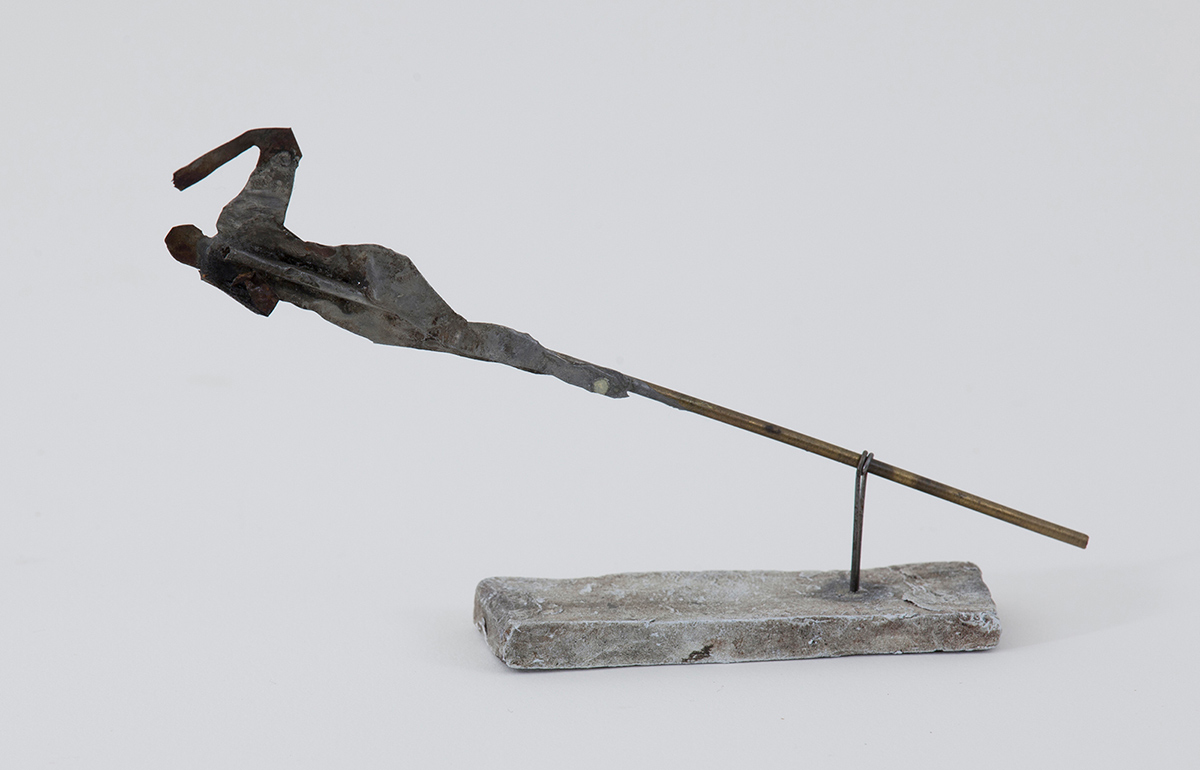 A slim metal pipe is held diagonally above a small rectangular base by a wire attachment. At the top of the pipe is the silhouette of a figure whose arm is raised in a curving motion as if swimming. The figure's legs appear to wrap around the pipe.
