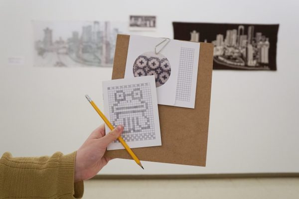 A hand holds up a brown masonite board with a small sketchbook and graph paper. A geometric frog is drawn on the cover by filling in squares of the graph paper. In the background, a brown and tan weaving of a city skyline hangs next to a sketch and xerox of the same image.