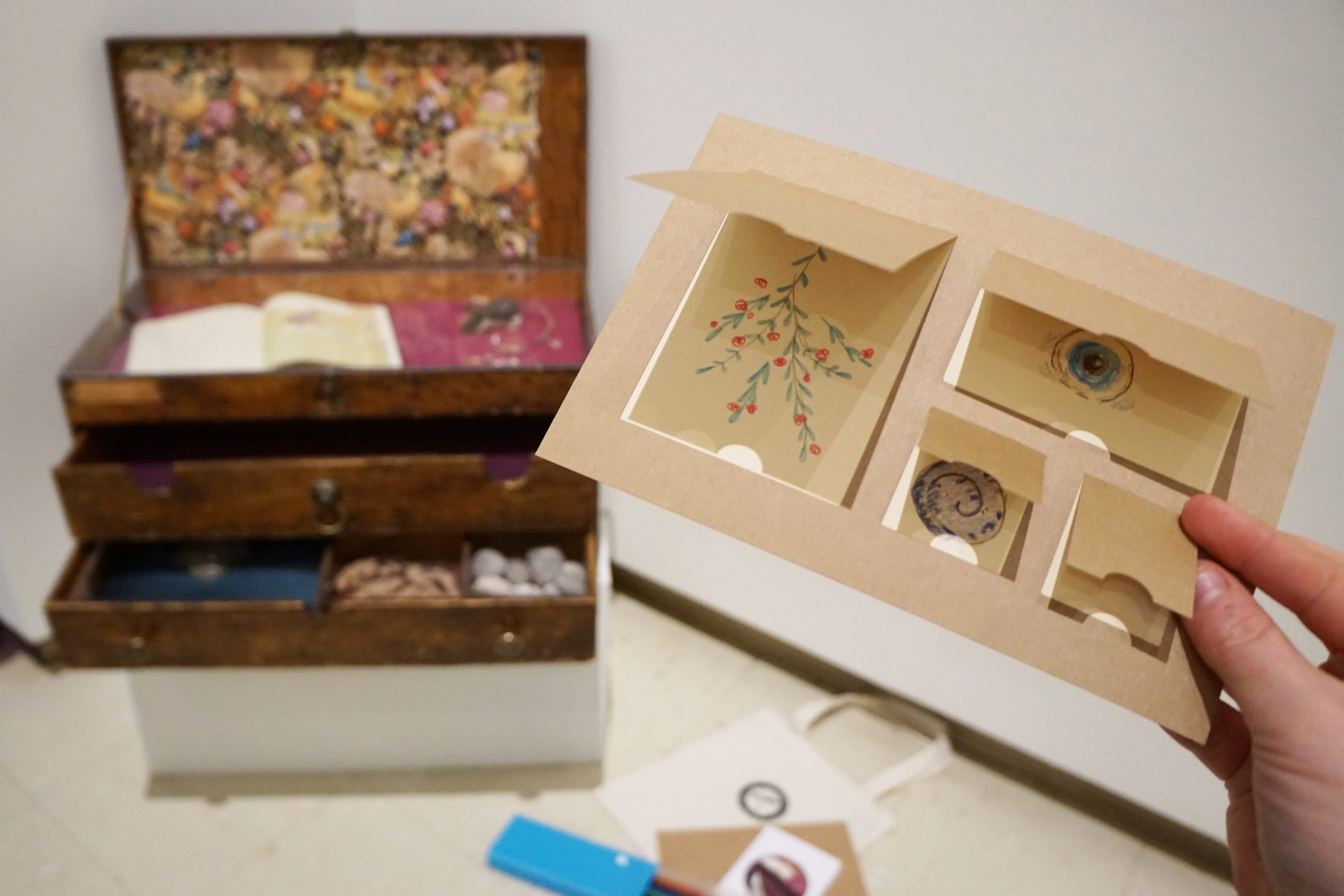 A hand holds a small card with five pop-out windows in a gallery. On the floor to the right, a small worn wooden chest with a hinged top is propped open to display an open book and life-sized felt mouse on plum-coloured velvet inside. Next to the artwork are pencils, a small canvas bag and an instructional card.