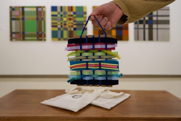 A hand holds a small weaving made of yarn and ribbon of many different colours, textures and thicknesses. Below on a bench rests two canvas bags. In the background, large weavings of colourful grid hang on a white wall.