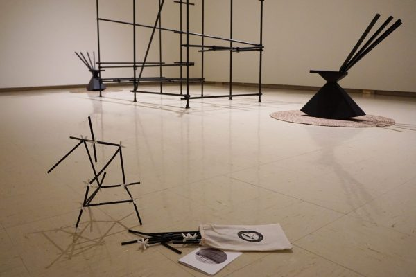 In the centre of a gallery is a large cage-like structure between two black sculptural rocking. On the floor in front of the installation is a small structure with black straws and white connectors, a drawstring bag and small card.