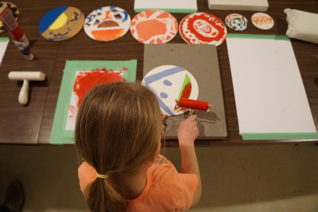 A child stands over a table inking-up a circular printing plate with face-like features. In their hand they hold a rubber roller with red ink. On the table there is a row of similar round plates that feature colourful hand-cut squiggles and shapes.