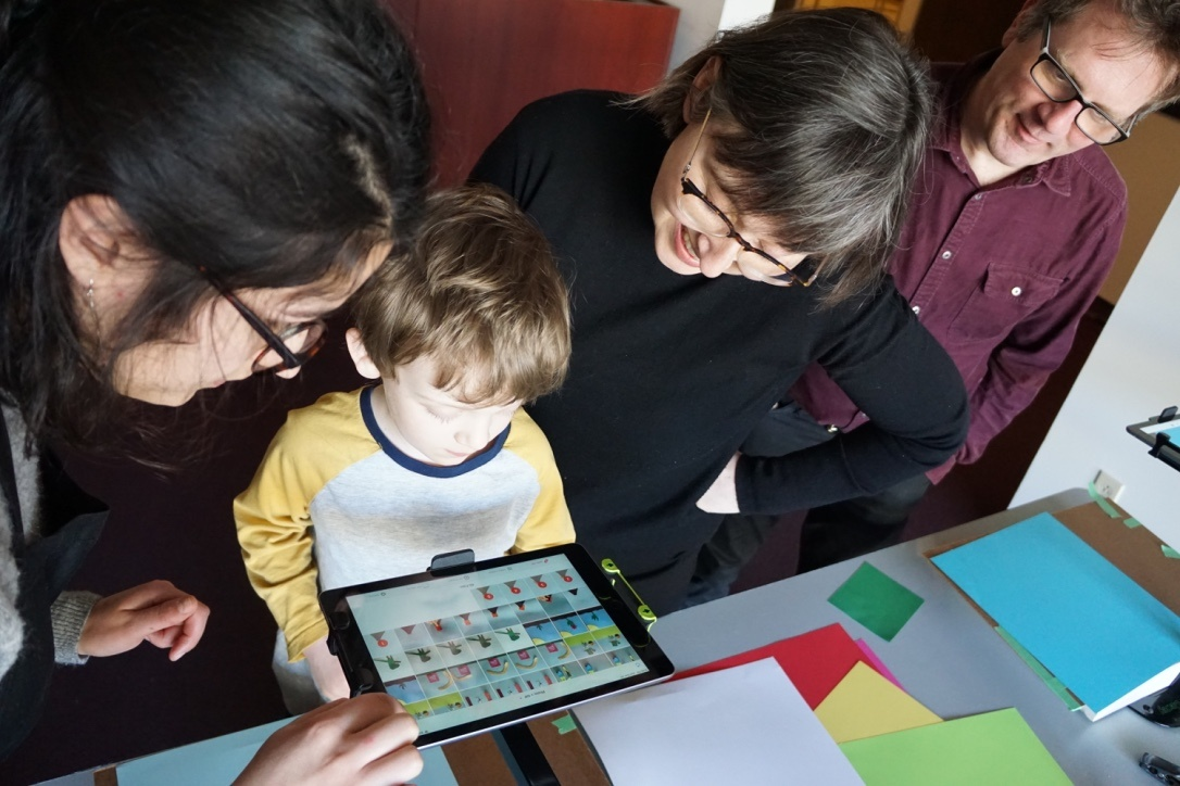A child and three adults gather around an iPad on a stand. On the iPad screen multiple frames of an animation are selected. Scattered on the table are sheets of colourful paper.