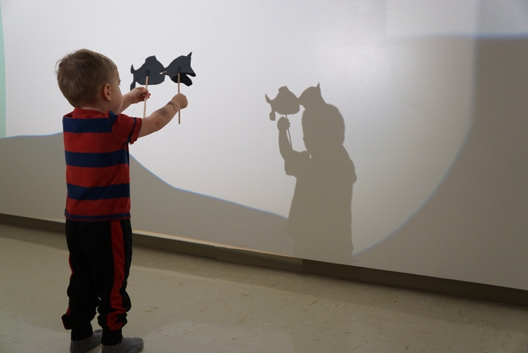 A small child stands in a darkened room facing an illuminated wall. In their hands they hold up paper fish taped to sticks. From behind them, a projected light casts their shadow against the wall.