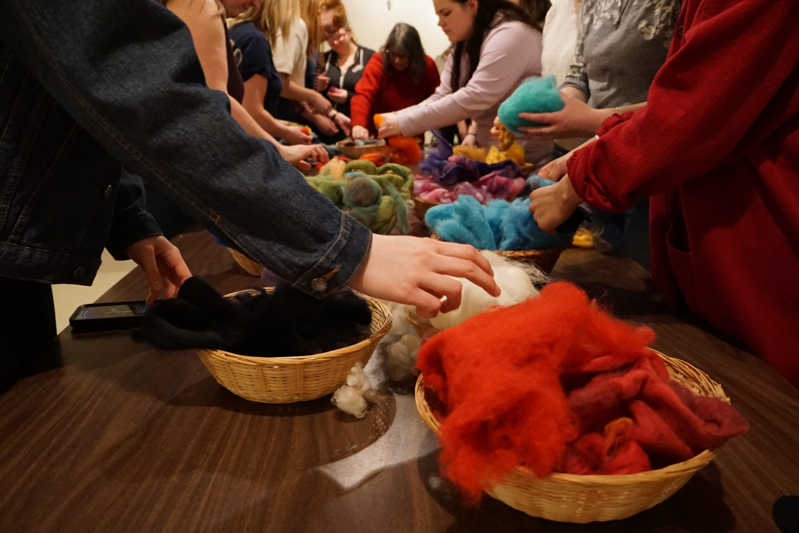 People crowd around a long table, reaching out to select colours from overflowing baskets of soft wool roving.