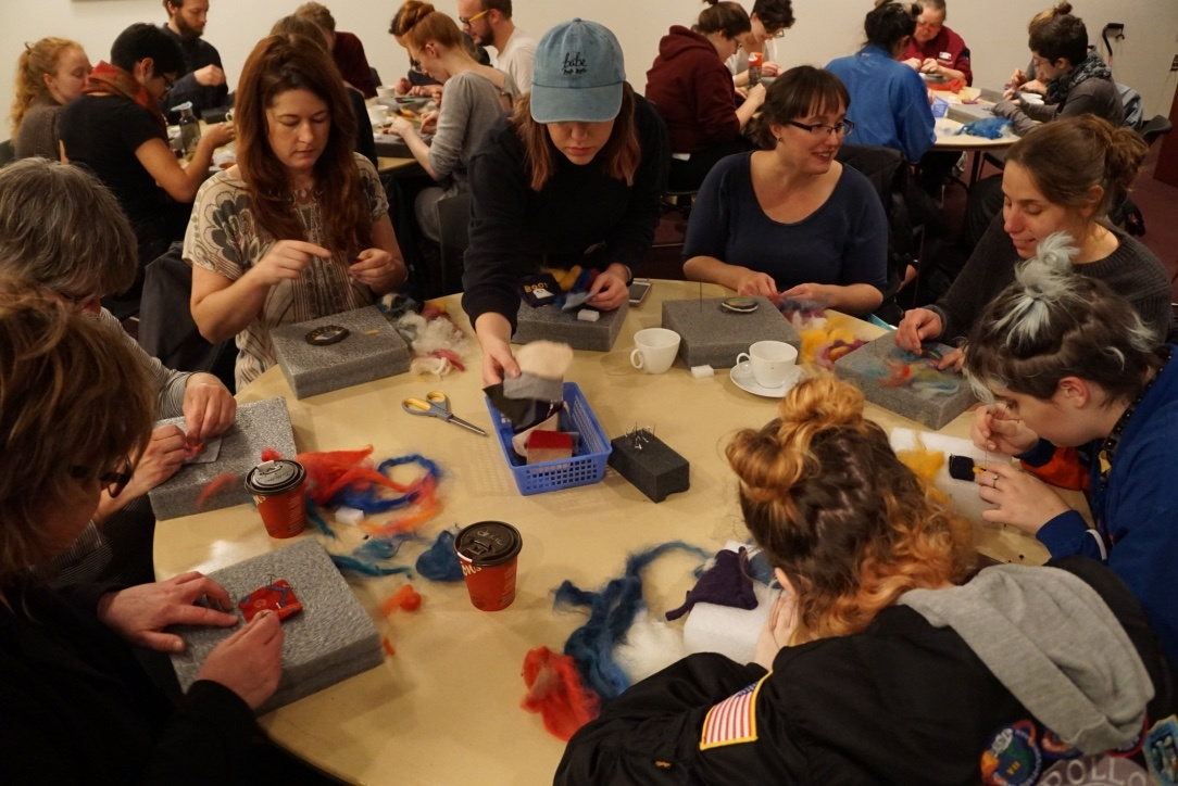 In a crowded room, people gather around circular tables to work on small needle felting projects.
