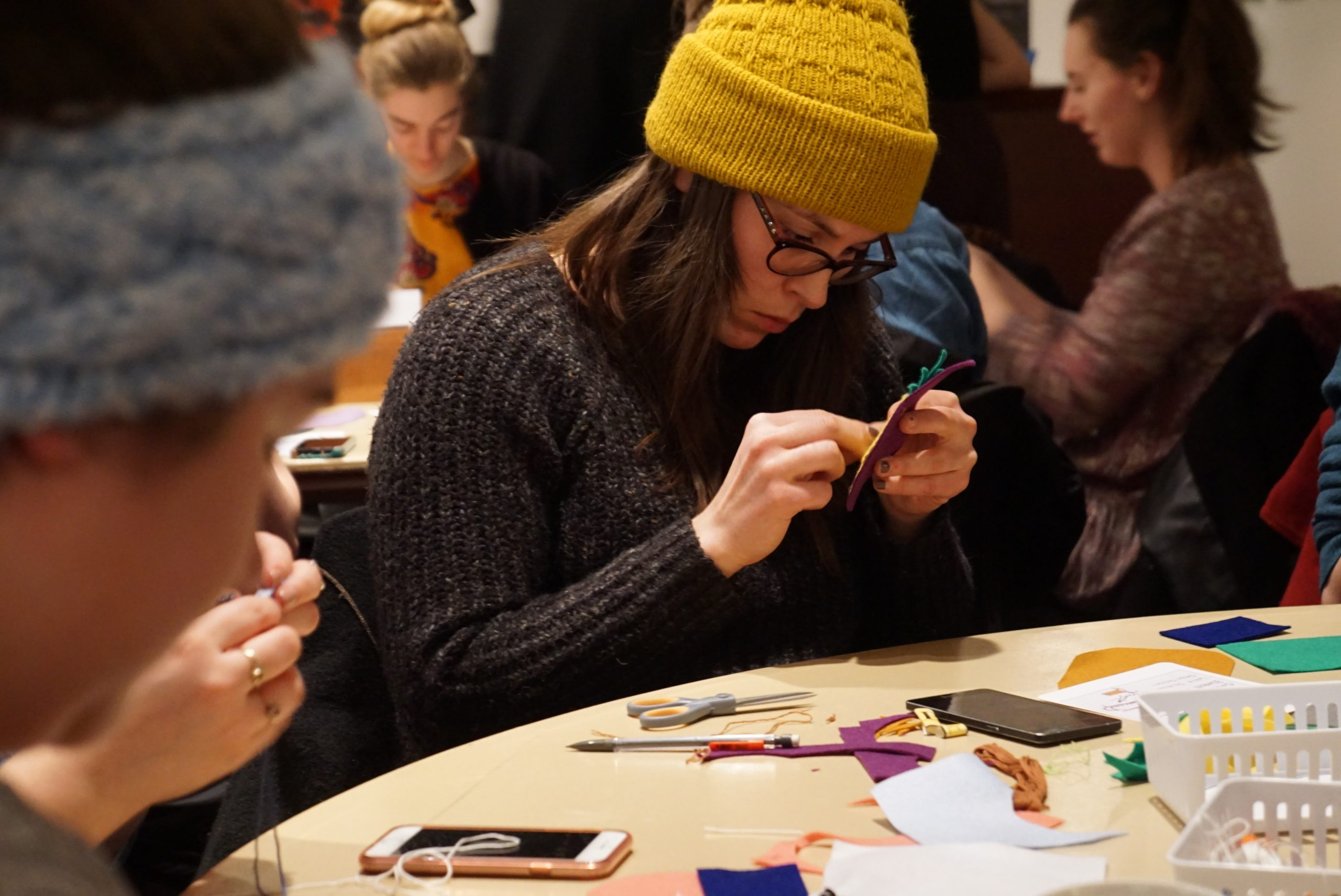 An adult sits working at a table. They are focused insanely on the sewing project in their hands.