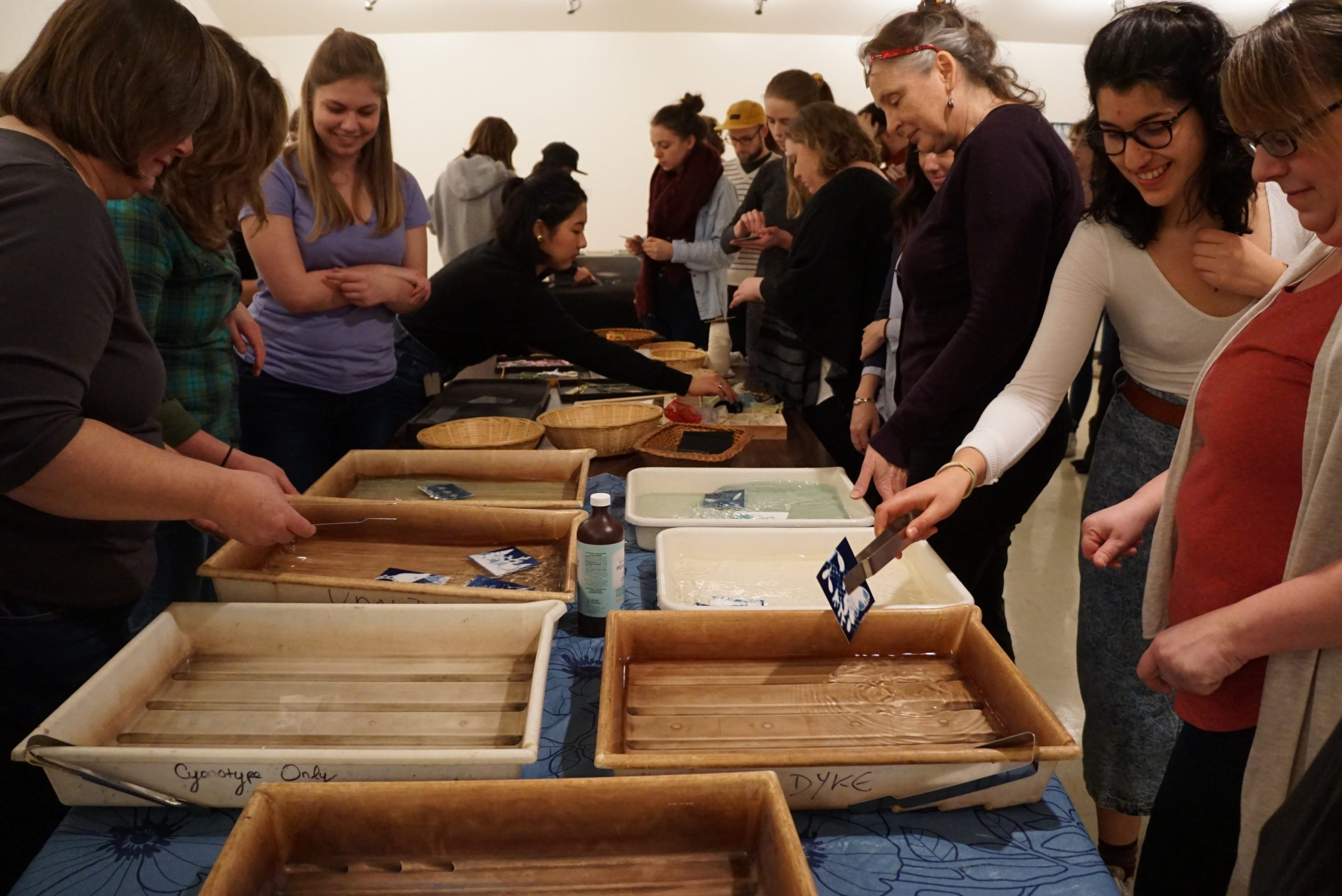 People crowd around a long table with two rows of plastic trays containing developing solution. One person who is smiling lifts a small blue and white cyanotype print from one of the trays using tongs. Nearby others look at the cyanotype prints floating in the various trays.
