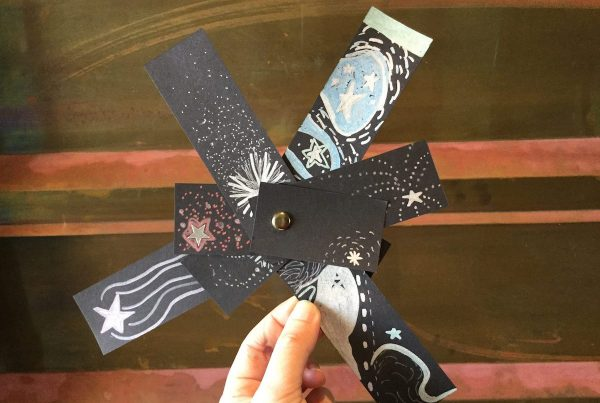Several pieces of black paper have stars drawn on them with metallic markers. The papers are held together with a gold brad, and help up by a hand.