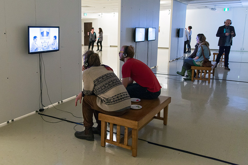 Two university students sit on a bench wearing headphones connected to a TV. In the background other gallery visitors watch another TV screen.
