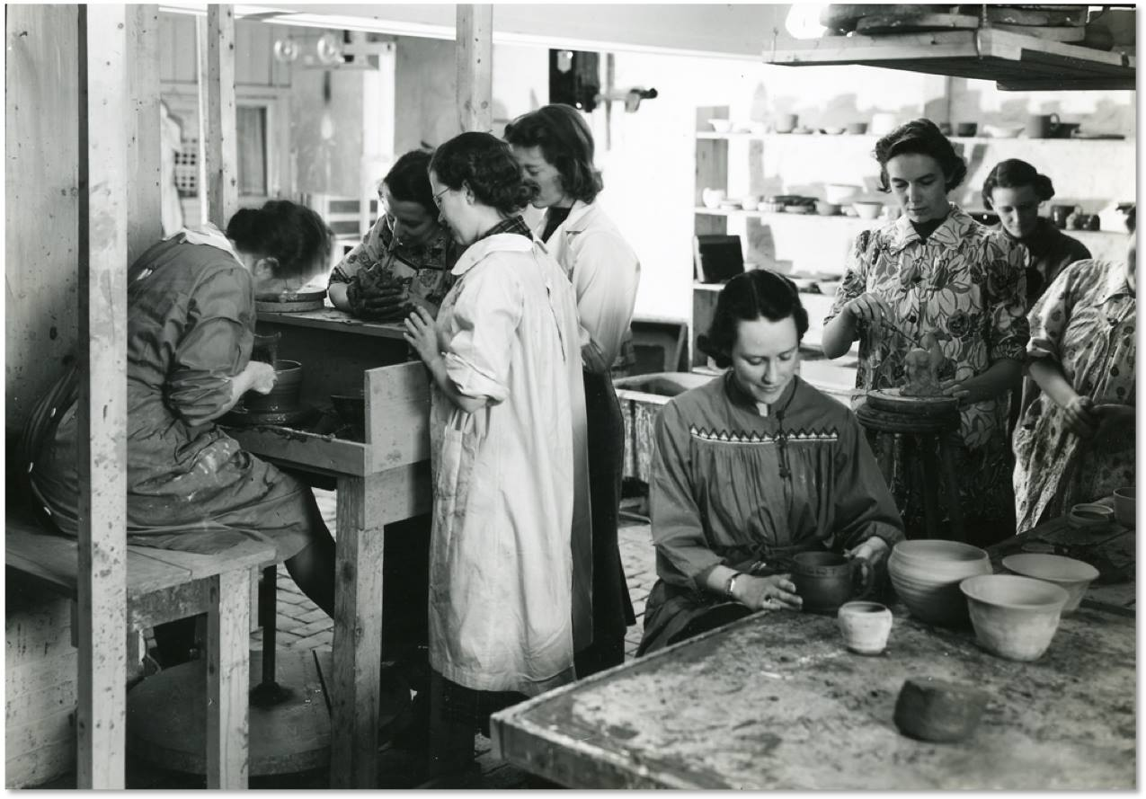 In this black and white photograph, a group of women work in a ceramics studio. One works at a kick wheel while others observe. Others work at a table or standing.