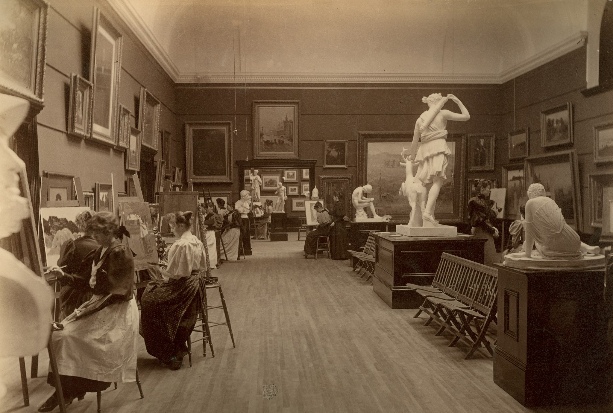 A sepia-toned photograph shows women seated at easels painting copies of the framed paintings on display in a gallery with a high ceiling. In the centre of the room plaster casts of classical Greek statues are displayed on a high plinth.