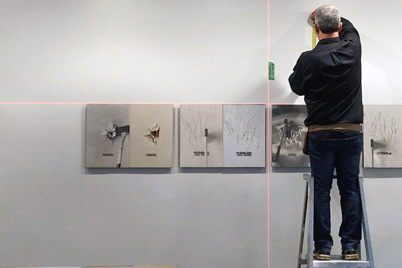 Gallery Preparator, Roxie stands on a ladder using a measuring tape above several artworks.