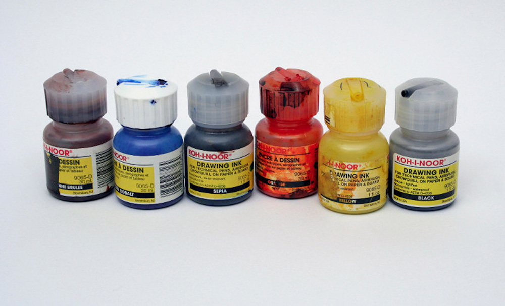 Five bottles of opened Koh-I-Noor drawing ink in brown, cobalt, Sephia, orange and yellow and one unopened black bottle.