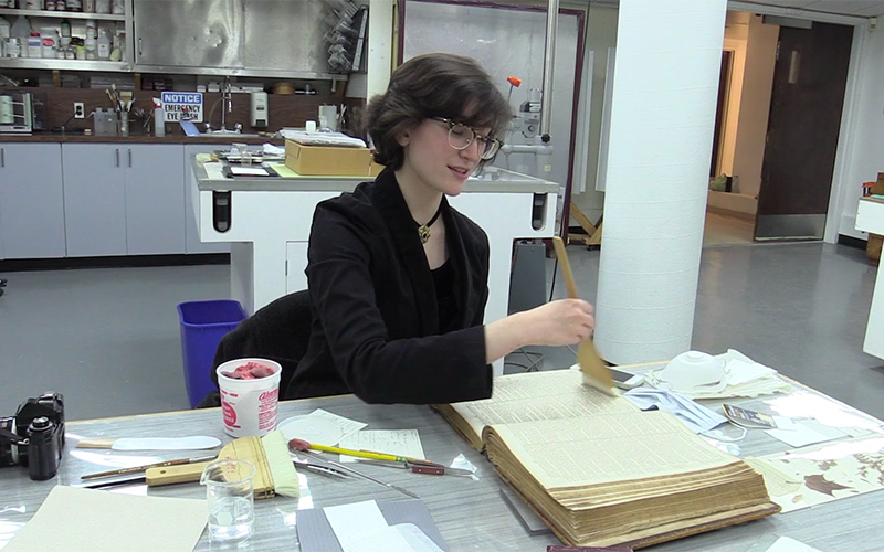 Grace sits in the conservation lab, using a large brush to clean a book.