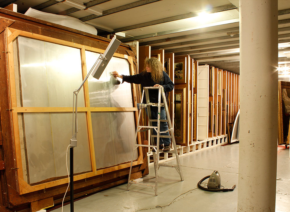 In a painting vault with rows of sliding panels, an art conservator stands on a ladder cleaning the back of a large painting. The painting is tall and wide, cradled in a wooden frame. A standing lamp on the floor illuminates the back of the painting.