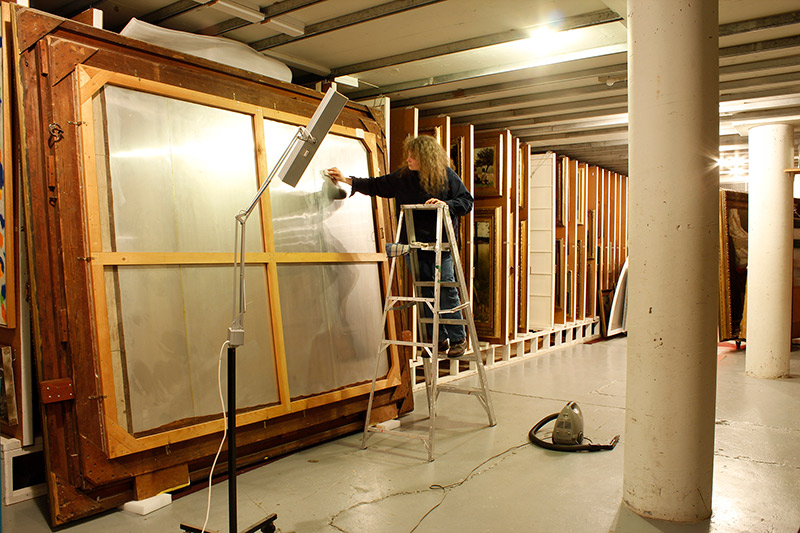 Jane Tisdale, Owens Art Gallery Conservator stands on a ladder while cleaning the back of a very large framed painting in the painting vault.