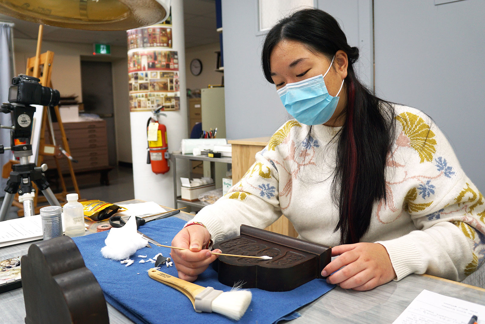 In an art conservation lab, a university student sits at a table cleaning a decorative wooden bookend. The student wears a blue face mask over their mouth and nose, and uses a cotton swab on a wooden dowel to delicately clean the surface of the wood.