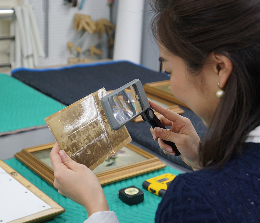An adult looks at a photograph of a group of people through a magnifying glass. The sepia photograph's glossy surface is creased. Behind the photograph, there is a table with framed paintings resting on green and black quilted fabric.