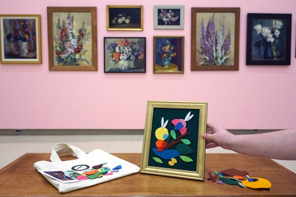 In a gallery, a hand holds a small gold frame upright on a table. Colourful pieces of felt including circle, leaf, petal, and branch shapes have been used to make a floral image within the frame. A row of floral paintings hang on the wall in the background.