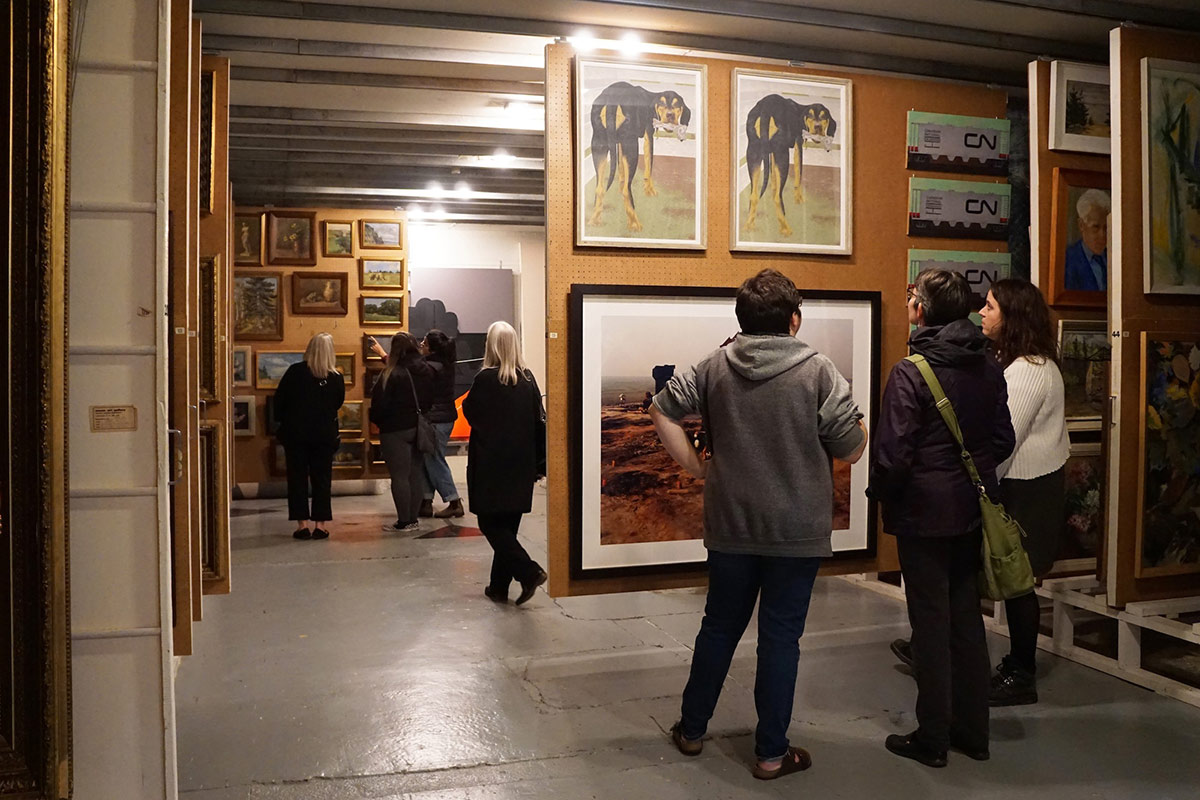 Adults stand in a small groups examining works in a gallery's painting vault. Panels hang in tight rows from ceiling rails. Two panels have been pulled out into view.