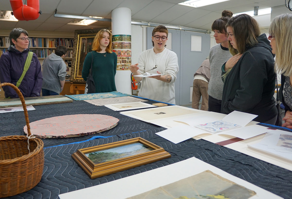 A group of adults gather around a large table covered in quilted fabric in an art conservation lab. In the center of the group, a person holds up a small sculptural object. On the table in front of the group are prints, drawings, paintings, small weavings and a woven basket.