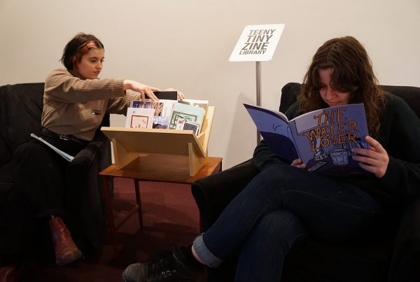 """Two adults sit in arm chairs. Between them is a small table with a wooden display shelf that holds a selection of small publications. While one of them reads a publication, the other peruses the shelf. Behind them is a sign with text that reads """"TEENY TINY ZINE LIBRARY""""."""