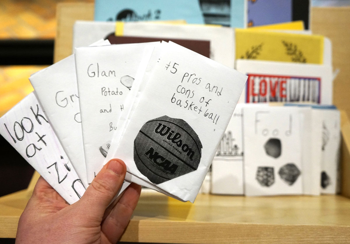A hand holds up four small black and white folded zines. In the background is a wooden shelf that displays more zines of various shapes and sizes.