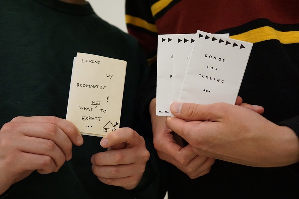 """A close up view of two pairs of hands, each holding small copies of zines with the covers facing outwards. One has """"LIVING W/ ROOMMATES & WHAT NOT TO EXPECT"""" written across the cover, the other is titled """"SONGS FOR FEELINGS."""""""