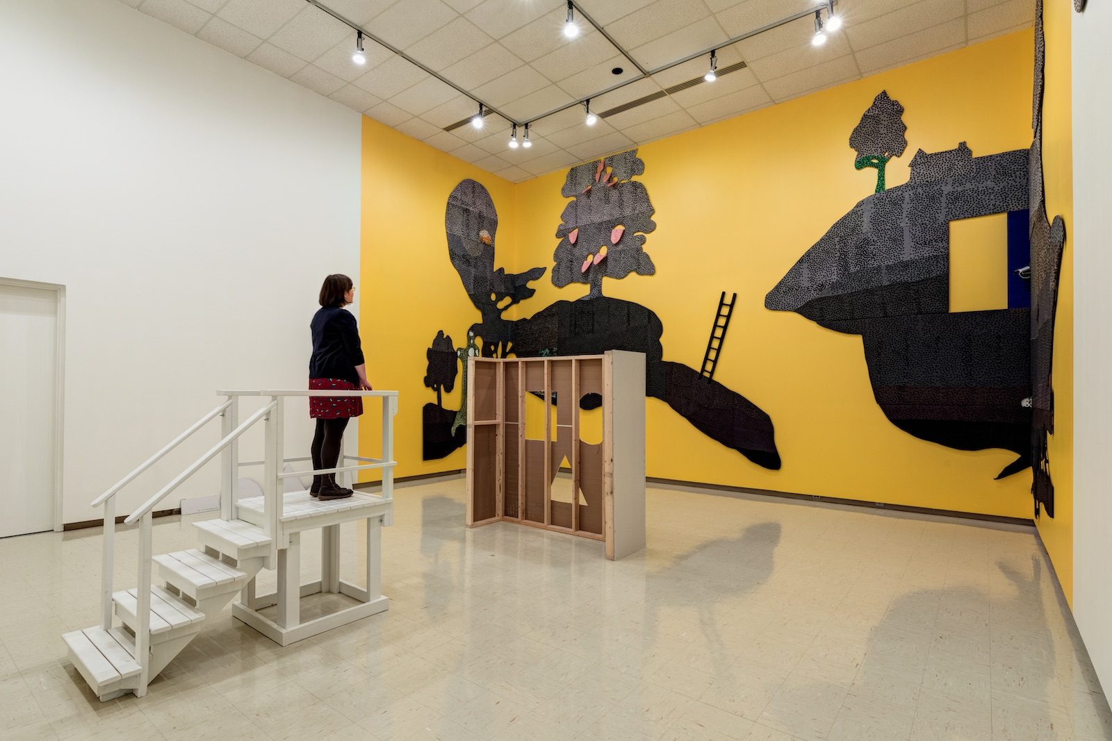 A gallery visitor stands on a white platform looking up to a silhouette of a whimsical landscape, against bright yellow walls. Between the viewer and the landscape is a false wall with a circle, square and triangle cut out.