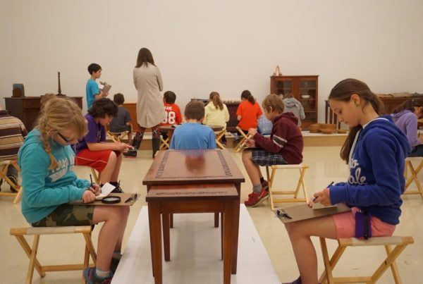 In a gallery, children sit on folding stools examining wooden furniture on display. They hold pencils and clipboards and work in small booklets. A studnet in the foreground holds the handle of a magnifying glass that rests on the clipboard on their lap.