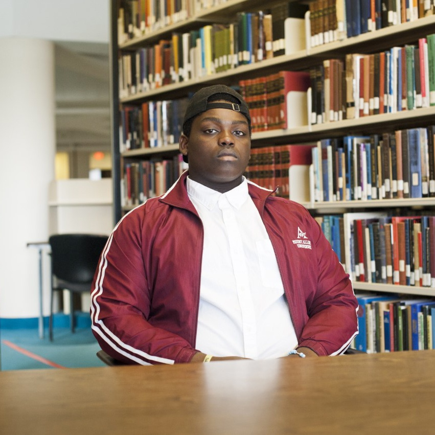 Portrait of Noah Lubendo wearing a backwards ball-cap and a Mount Allison garnet athletic jacket. Noah is seated at a table near library stacks.
