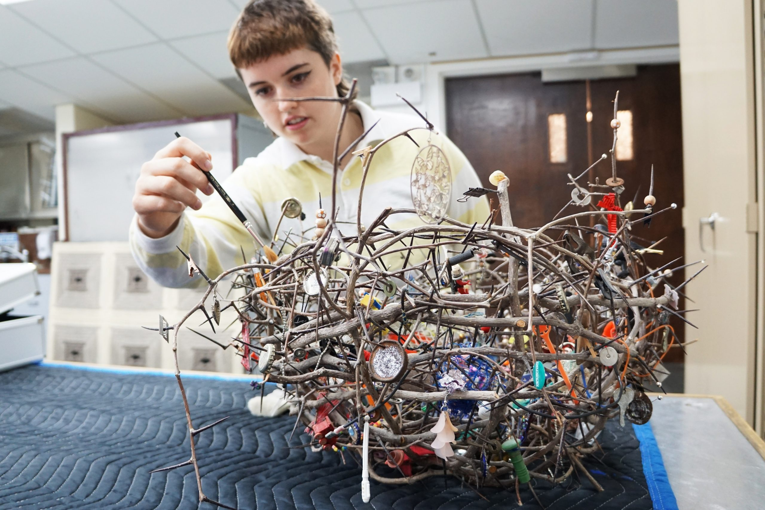 A university student stands over a table cleaning a sculpture using a small brush. The sculpture resembles a bird's nest made of twigs and branches. Ornaments and small objects of various shapes, colours, and sizes hang from its branches. The sculpture rests on the table atop a piece of quilted fabric in an art conservation lab.