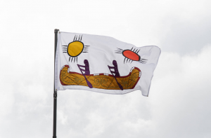 A brightly coloured flag flies against a cloudy sky. The image on the flag features two suns, one yellow and one red, and two figures paddling a canoe.