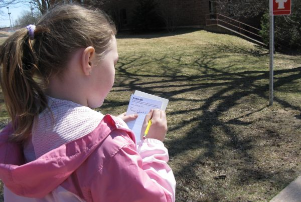 """A young person in a pink hooded jacket stands outside facing a sign with the symbol of a fire hydrant. They are making notes on a narrow card with the heading """"Smooth""""."""