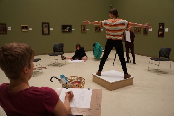 A clothed figure model stands in the centre of a gallery on top of a wooden plinth, with their feet apart and arms outstretched. Adults sit in a circle around the model, drawing them from observation.