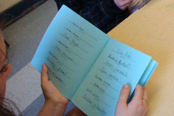 A young person looks at a book with blue pages. The facing pages each contain a list of handwritten names.