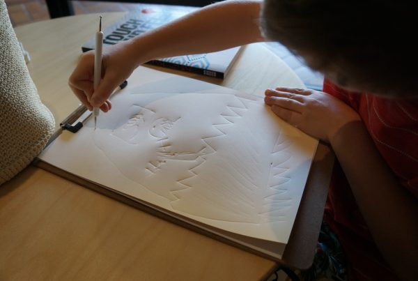 A close-up of a child's hands using a tactile drawing tool to emboss lines of a drawing into a sheet of white paper.