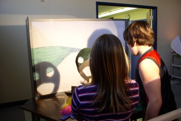 Two children stand in a darkened room in front of a small screen with a projected drawing. One of them holds a paper smiley face that casts a shadow of the smiley face onto the screen.