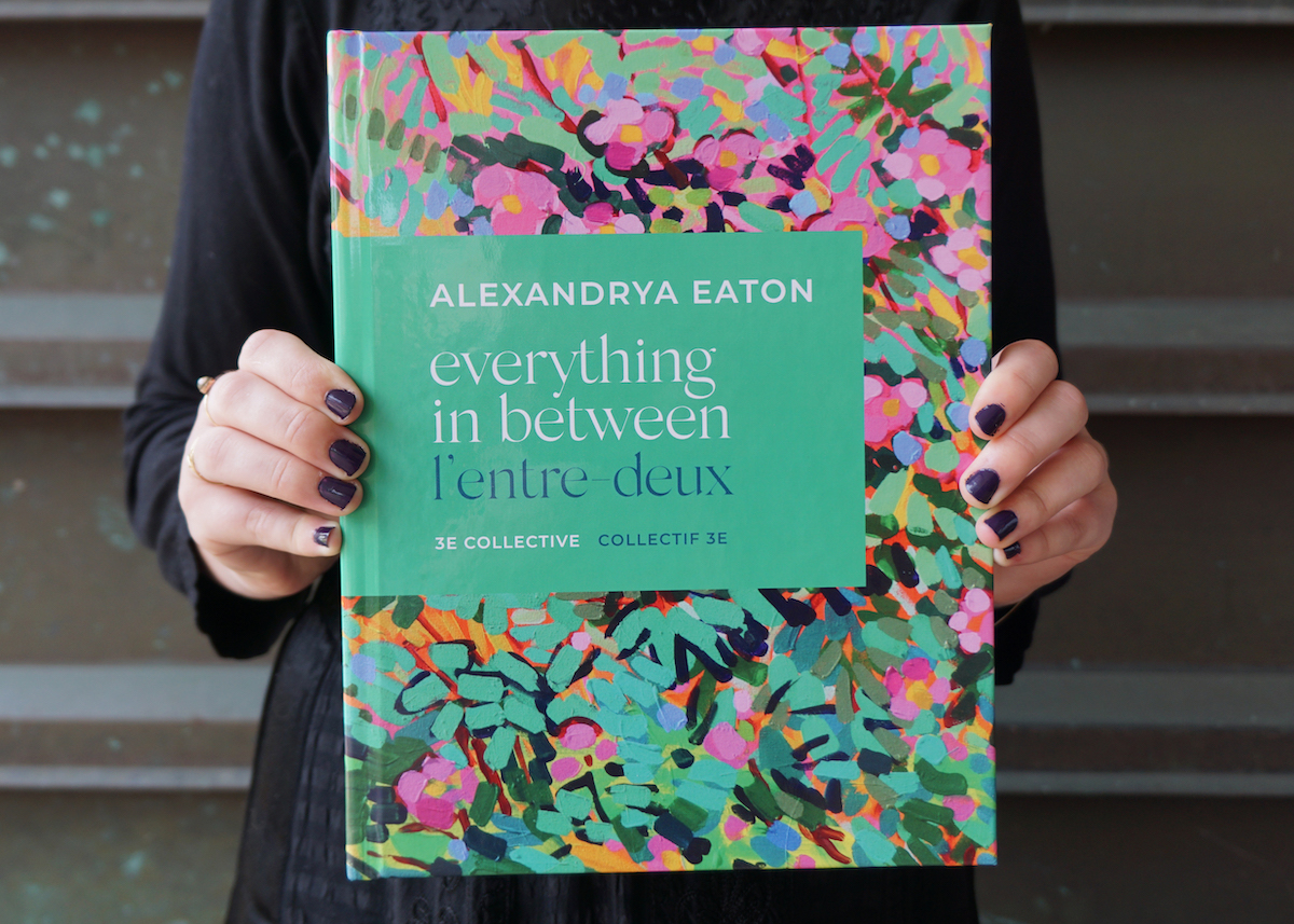 """Two hands hold a hardcover book. The cover has text that reads """"Alexandrya Eaton Everything In Between l'entre deux 3e collective"""" on a green square surrounded by a painting of vibrant pink flowers and lush greenery."""