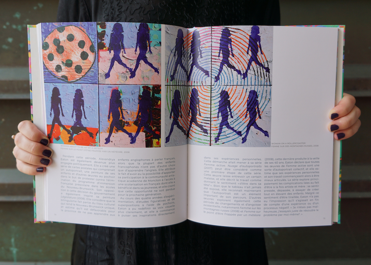 Two hands hold open a book. Inside there is a grid of paintings of women walking accompanied by an essay.