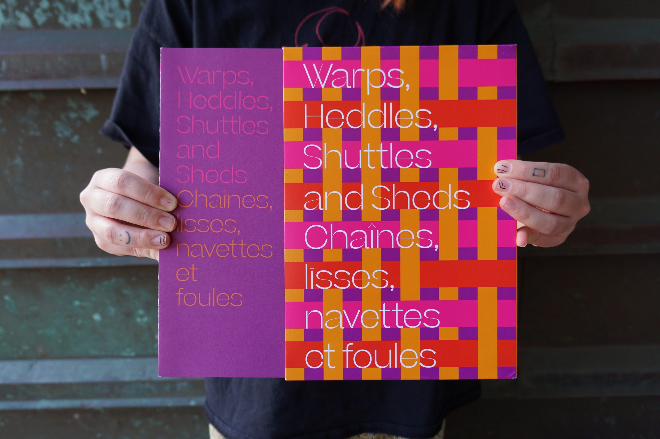 """A pair of hands removes a publication with a purple cover with the words """"Warps, Heddles, Shuttles and Sheds"""" in pink and """"Chaîne, Līsses, navettes et foules"""" in orange, from a slip case. In white text """"Warps, Heddles, Shuttles and Sheds Chaîne, Līsses, navettes et foules"""" sits atop woven bands of vibrant orange, pink and red against a purple background on the slipcase."""